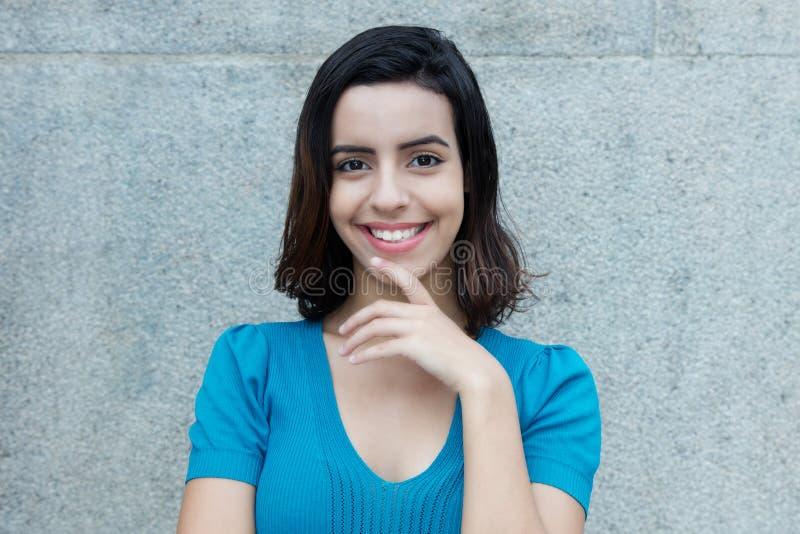 Schöne lächelnde hispanische Frau, die Kamera betrachtet lizenzfreie stockfotografie
