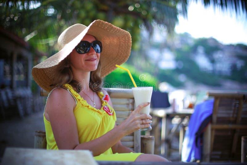 Schöne lächelnde junge Frau in der Sonnenbrille, die Hut mit einem Cocktail am Strandcafé trägt stockfotos