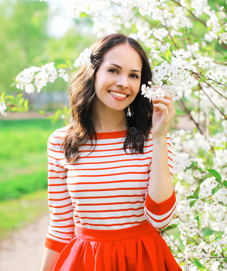 Schöne lächelnde junge Frau des Porträts in blühendem Frühlingsgarten stockfoto