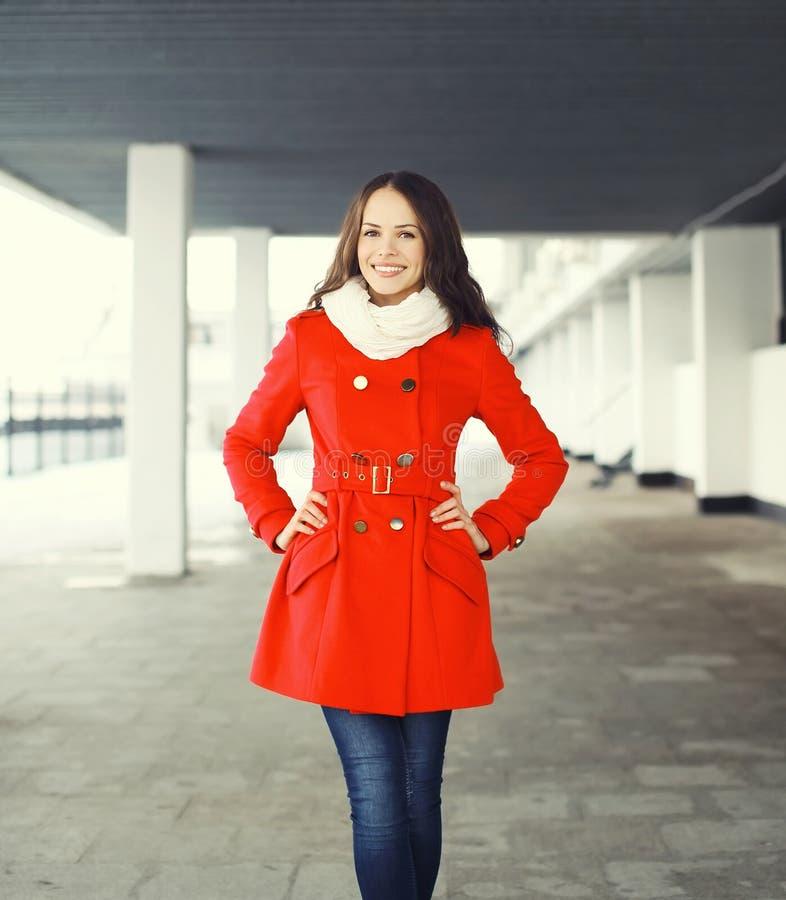 Schöne lächelnde junge Frau, die einen roten Mantel und einen Schal trägt stockfotos