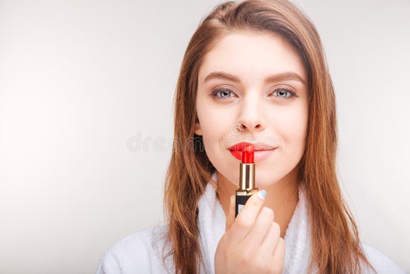 Schöne lächelnde junge Frau im Bademantel unter Verwendung des roten Lippenstifts stockfoto