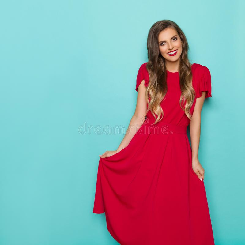 Schöne lächelnde junge Frau im langen roten Kleid stockbild