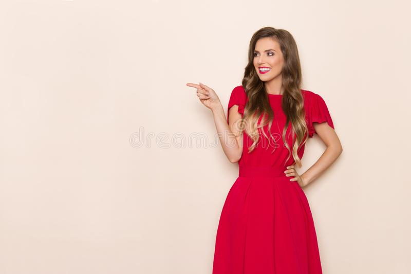 Schöne lächelnde junge Frau im roten Kleid ist weg zeigend und schauend stockfotografie