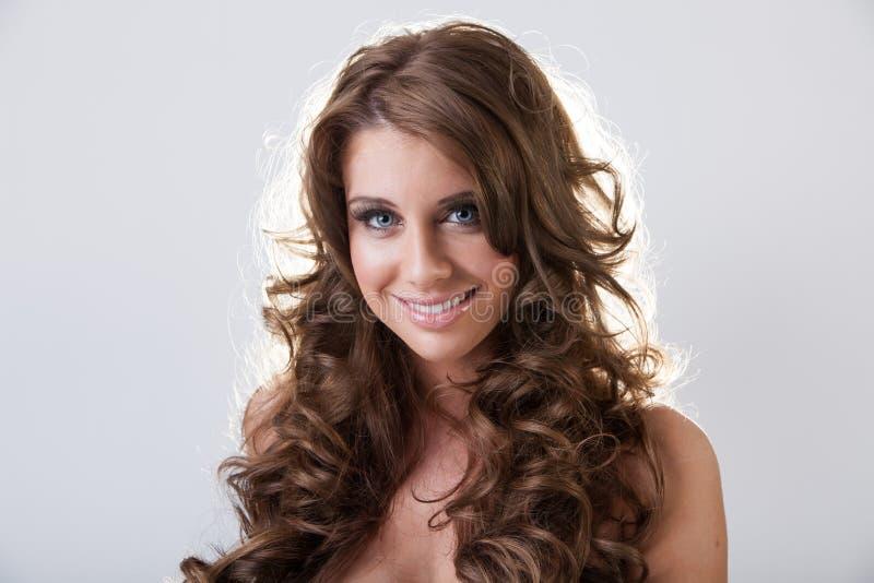 Schöne lächelnde junge Frau mit dem langen gelockten Haar stockfotografie