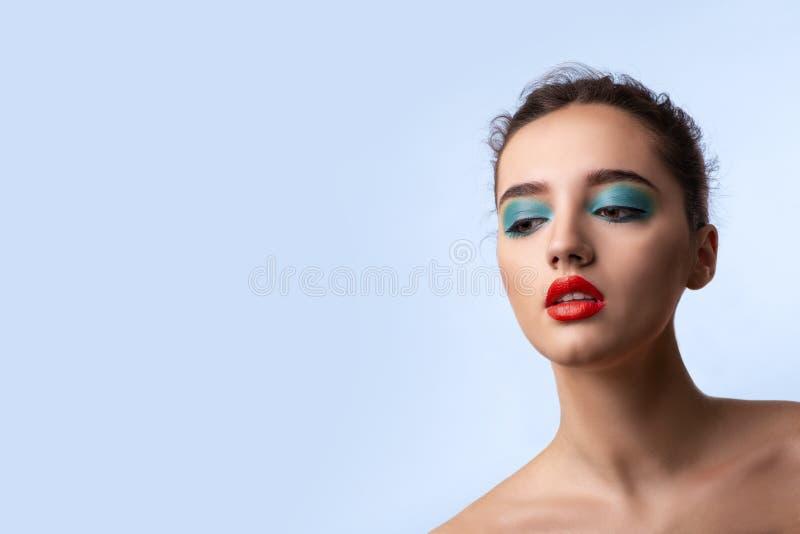 Schöne lächelnde junge Frau mit hellem Make-up auf blauem backgrond im Studio lizenzfreies stockfoto