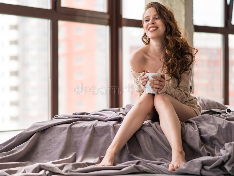 Schöne lächelnde junge Frau mit natürlichem bilden und lange Wimpern hält eine Schale mit whiile Sitzen des Kaffees oder des Tees stockbild