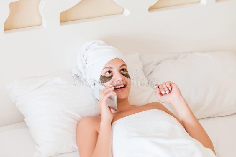 Schöne lächelnde junge Frau mit Unteraugenklappen und Unterhaltungshandy im Bademantel, der im Bett liegt Glückliches Mädchen, da lizenzfreies stockbild