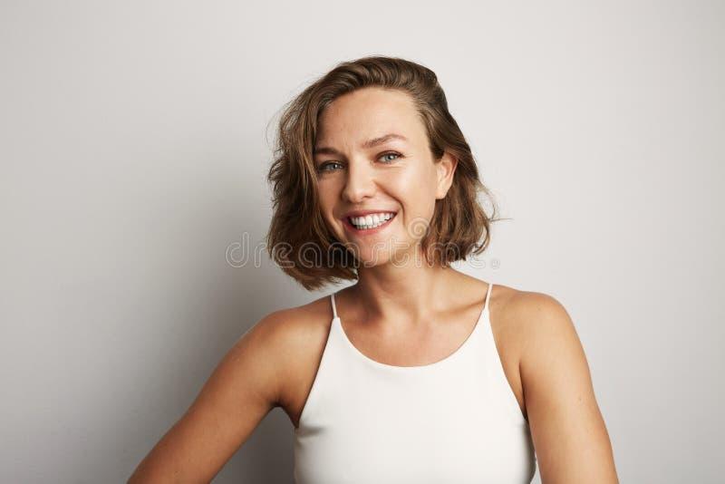 Schöne lächelnde junge Frau in weißem mit buntem Kranz auf Kopf lizenzfreies stockfoto
