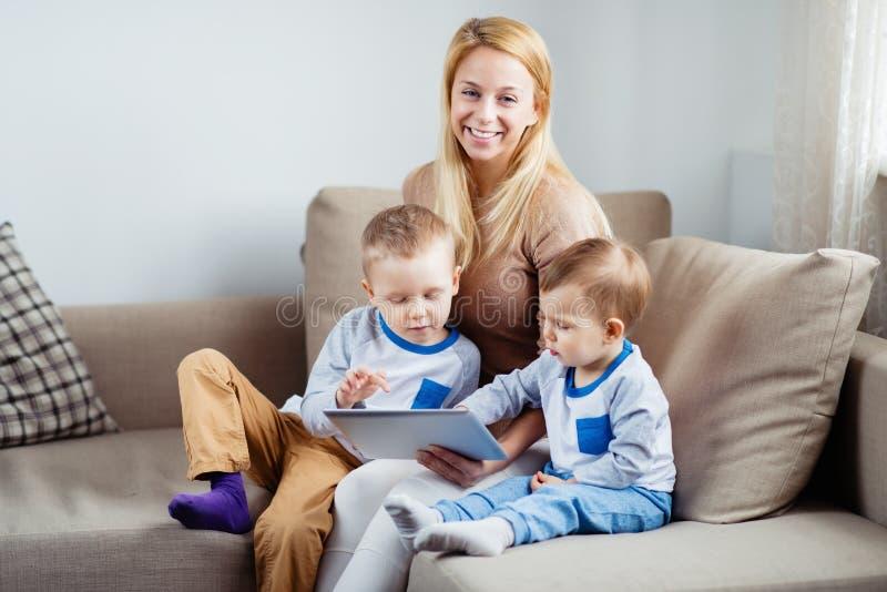 Schöne lächelnde Mutter mit ihren Söhnen, die digitale Tablette spielen stockbild