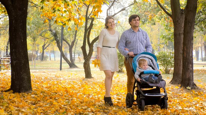 Schöne lächelnde Paare mit dem Baby, das auf Blätter am Herbstpark geht stockbild