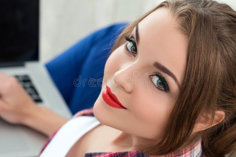 Schöne lächelnde Studentin, die on-line-Bildungsservice verwendet lizenzfreie stockfotografie