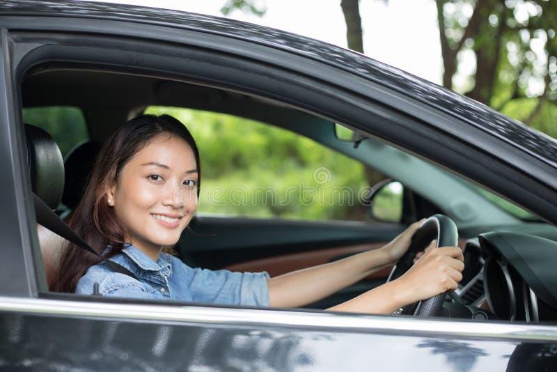 Schöne lächelnde und genießende Asiatin Autofahren auf Straße lizenzfreie stockbilder