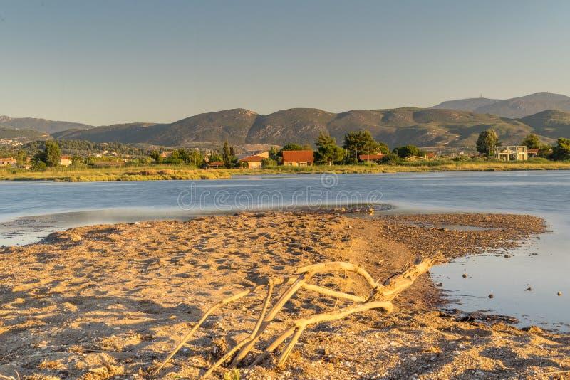 Schöne Landschaft in dem Sumpfgebiet von Oropos in Griechenland mit traditionellen alten und bunten Häusern gegen den See lizenzfreie stockbilder