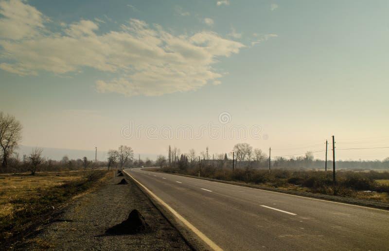 Schöne Landschaft der Landseitenstraße mit Bäumen in der Winterzeit bei Sonnenuntergang Aserbaidschan, Kaukasus, Sheki, Gakh, Zag stockbilder