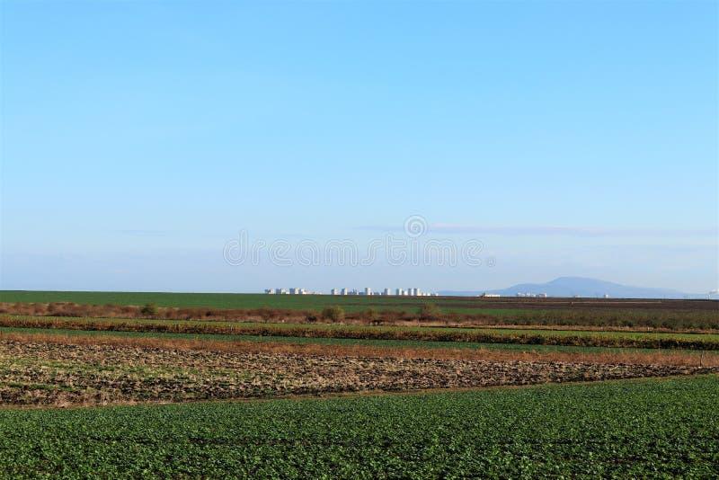 Schöne Landschaft, klares blaues Himmel-, Grünes und Braunesgepflogenes Feld in Bulgarien Auf dem Hintergrund ist Stadt Burgas lizenzfreie stockfotos