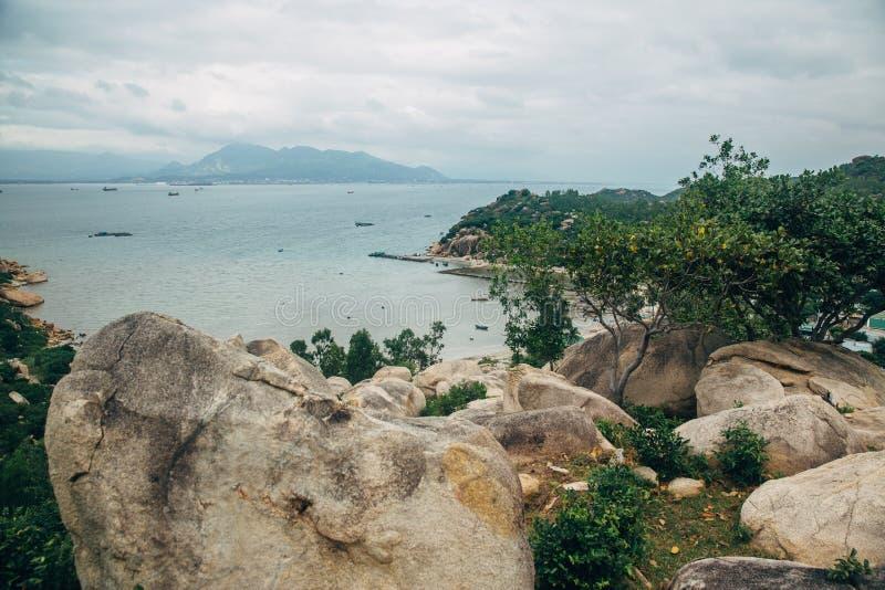 Schöne Landschaft mit Ansicht von Ozean, perfekter Strand, große Steine, Bäume, azurblaues Wasser Konzept von Energie Konzeptreis lizenzfreie stockbilder