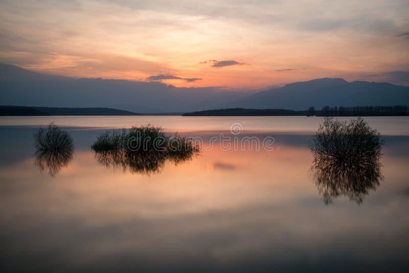 Schöne Landschaft mit brennendem Sonnenuntergang über einem See Ansicht von der Küste - Bild lizenzfreies stockfoto