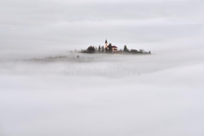 Schöne Landschaft Sloweniens mit Nebel und Kirche morgens lizenzfreie stockfotos