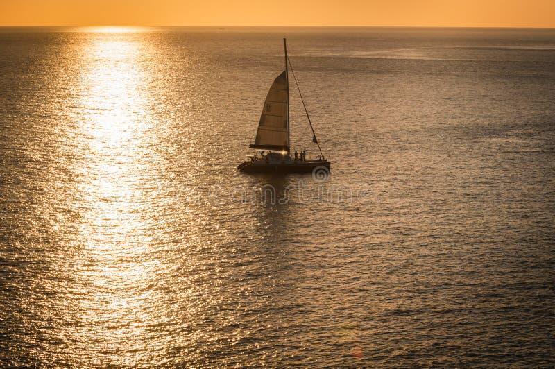 Schöne Landschaft und tropisch Yacht oder Segelboot über dem Seesonnenuntergang mit der Sonnenlichtreflexion auf dem Wasser lizenzfreie stockfotos