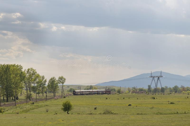 Schöne Landschaft, Zugfahrten durch ein schönes grünes Feld und Bäume, Sonnenstrahlen brechen durch die Wolken und den dunkelblau stockfotos