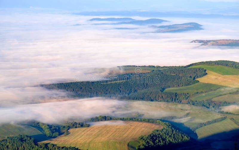 Schöne Landschaftsansicht von Hügeln und Wiesen, Nebel und Wolken lizenzfreie stockbilder