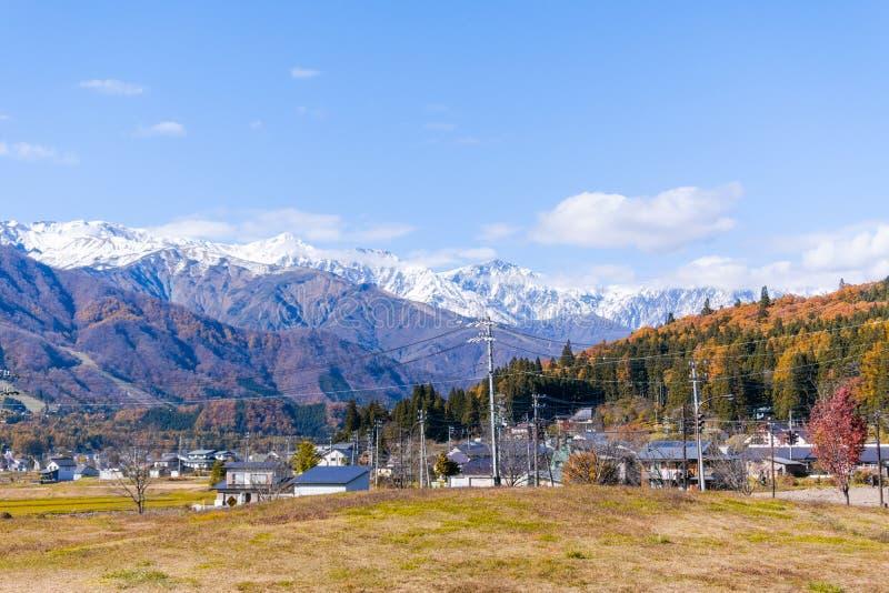 Schöne Landschaftsansicht von Hakuba im Winter mit Schnee auf dem Gebirgs- und des blauen Himmelshintergrund in Nagano Japan lizenzfreie stockfotografie