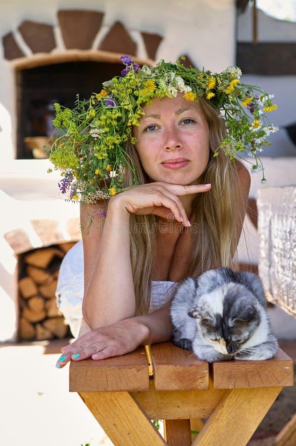 Schöne lang-weiße Haarfrau im weißen Kleider- und Blumenkranz, der auf einer Holzbank mit netter flaumiger Katze im Yard von Ihre stockfoto