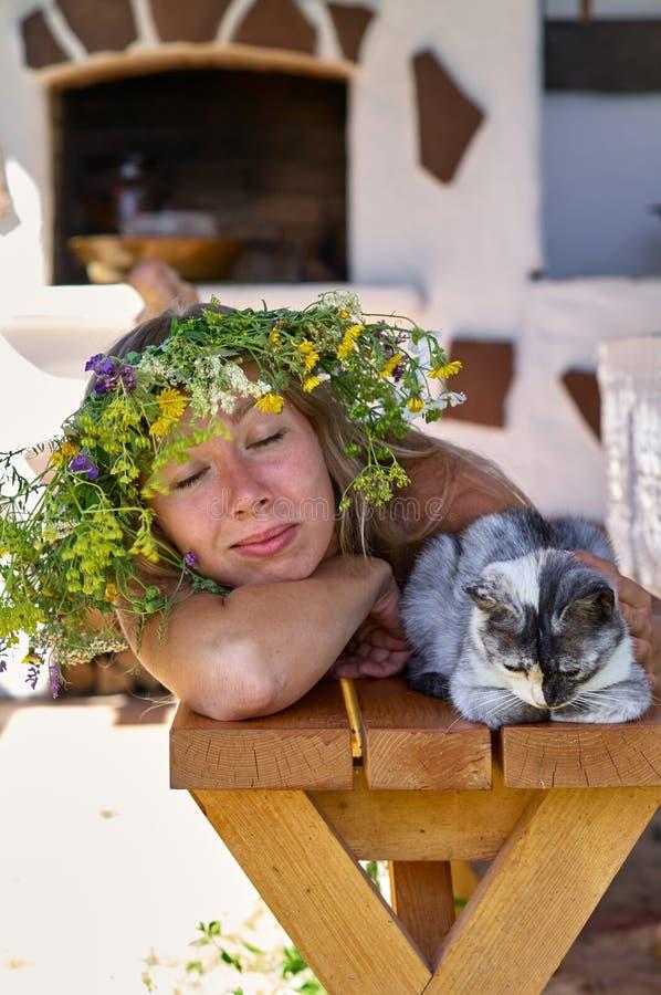 Schöne lang-weiße Haarfrau im weißen Kleider- und Blumenkranz, der auf einer Holzbank mit netter flaumiger Katze im Yard von Ihre stockbilder