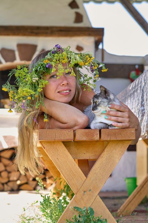 Schöne lang-weiße Haarfrau im weißen Kleider- und Blumenkranz, der auf einer Holzbank mit netter flaumiger Katze im Yard von Ihre lizenzfreies stockfoto