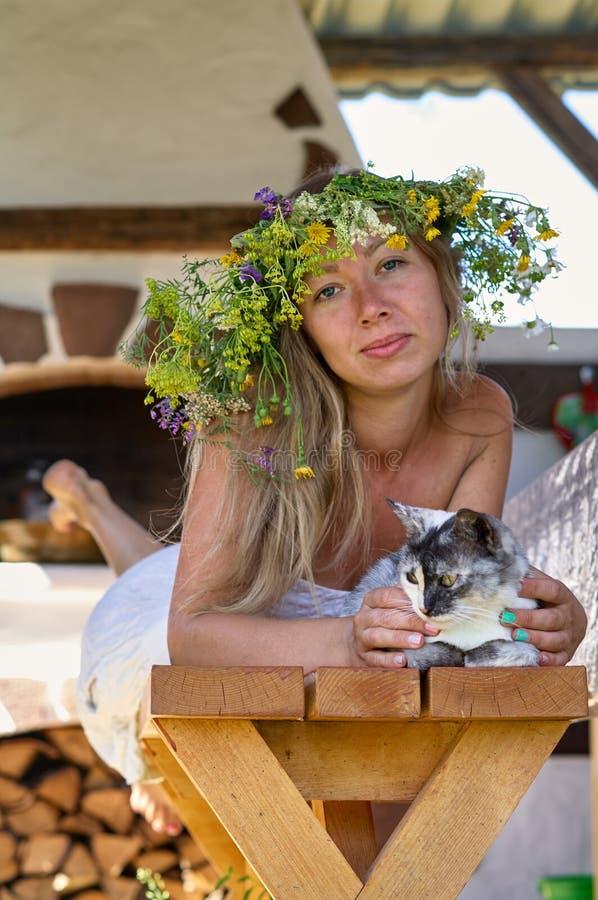 Schöne lang-weiße Haarfrau im weißen Kleider- und Blumenkranz, der auf einer Holzbank mit netter flaumiger Katze im Yard von Ihre lizenzfreies stockbild