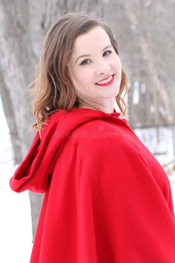 Schöne langhaarige Frau im roten Kap draußen im Winter stockfotos