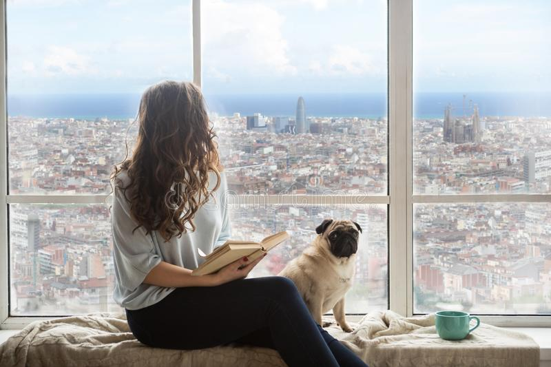 Schöne langhaarige Frau mit ihrem Hund, der Ansicht Barcelonas Spanien außerhalb des Fensters genießt stockfoto