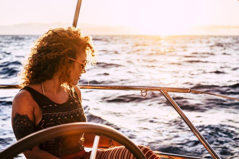 Schöne schöne, lockige, blonde erwachsene Frau, die den Ozean aussieht und eine Reise mit dem Segelboot unternimmt - moderne Gene lizenzfreies stockfoto