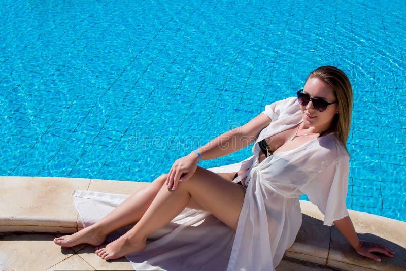 Schöne luxuriöse lächelnde junge Frau in einem weißen Strandmantel und -Sonnenbrille, die am Swimmingpool an sitzen und stillsteh lizenzfreie stockfotos