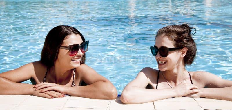 Schöne Mädchen in den Badeanzügen, die Spaß im Pool haben Seashells gestalten auf Sandhintergrund lizenzfreie stockfotografie