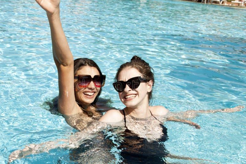 Schöne Mädchen in den Badeanzügen, die Spaß im Pool haben Seashells gestalten auf Sandhintergrund lizenzfreie stockbilder