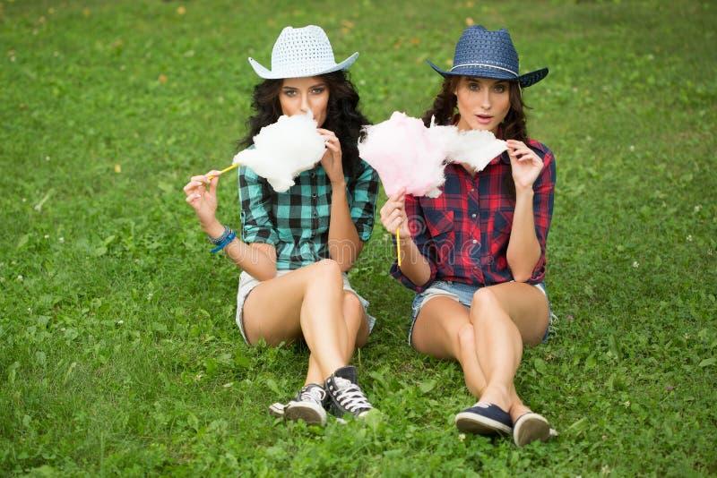 Schöne Mädchen in den Cowboyhüten Zuckerwatte essend lizenzfreie stockbilder