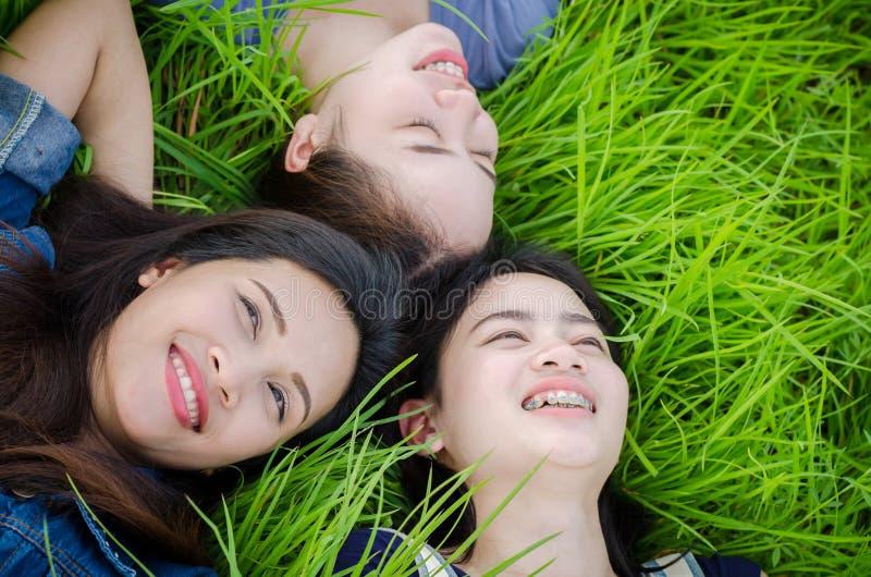 Schöne Mädchen, die auf Rasenfläche liegen stockfotografie