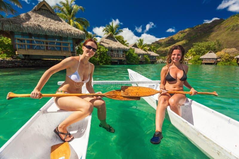 Schöne Mädchen im Bikini, der auf einem Kanu am tropischen bezüglich sich entspannt stockbild