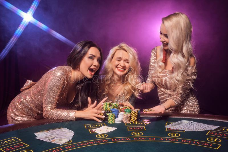 Schöne Mädchen mit perfekte Frisuren und helles Make-up werfen Stellung an einem Spieltisch auf Kasino, Poker stockbilder