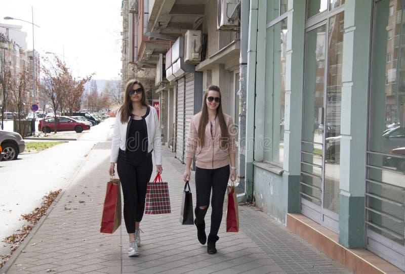 Schöne Mädchen sind lächelndes Hinuntergehen die Straße lizenzfreie stockfotos