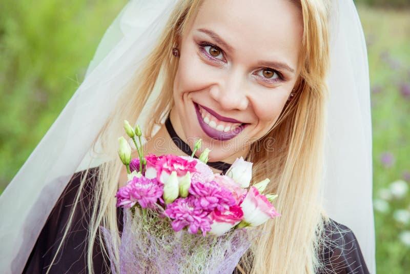 Schöne Mädchenbrautblondine in der gotischen Art mit einem Blumenstrauß in der Hand im Sommer lizenzfreies stockbild