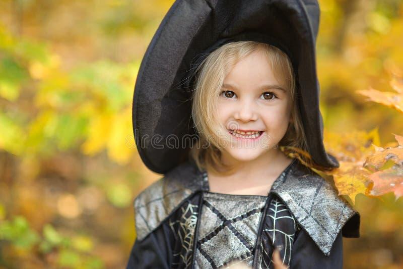Schöne Mädchenhexe kleines Mädchen, in dem Kostüm Halloween im Freienfeiern und einen Spaß haben Kindertrick oder -behandlung lizenzfreie stockfotos