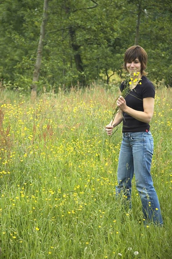 Schöne Mädchensammelnblumen stockfotos