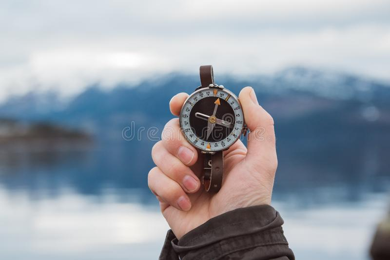 Schöne männliche Hand hält einen Magnetkompass vor dem hintergrund des Berges und eines Sees Das Konzept des Findens stockfotografie