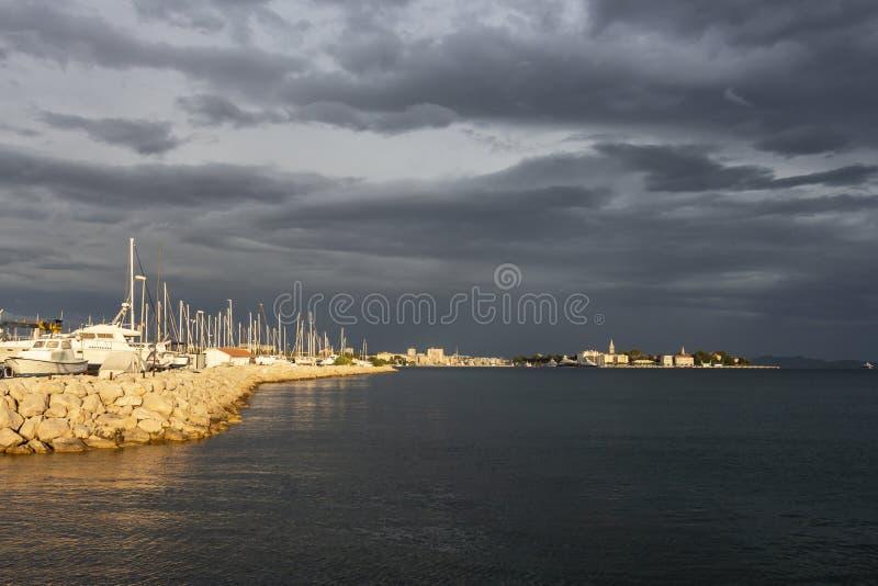 Schöne magische Ansicht von Zadar-altstadt über einem Meer und Hafen mit dunklen Wolken und Sonnenuntergang beleuchten stockfotografie