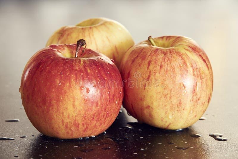 Schöne Makrophotographie von drei gelb-roten frischen Äpfeln auf dunklem Holztisch stockfoto