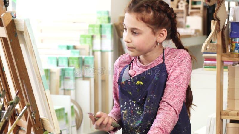 Schöne Malerei des kleinen Mädchens auf dem Gestell unter Verwendung der Ölfarben am Kunststudio stockbild