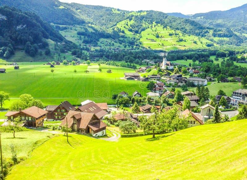 Schöne, malerische, erstaunliche Sommertagesansicht von Lungern-Dorf seine katholische Kirche Pfarrkirche vom Zugfenster umgebend lizenzfreie stockbilder