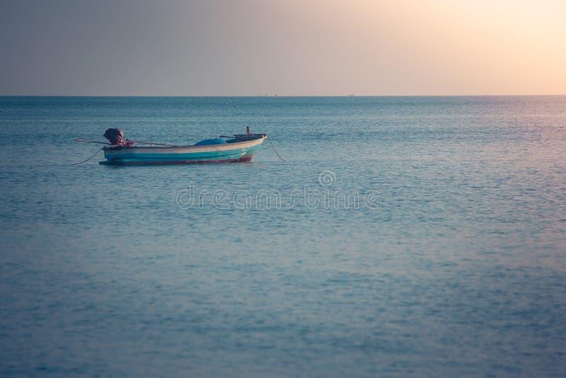 Schöne Meerblickansicht des Fischerbootes schwimmend auf das Meer mit Sonnenunterganglicht im Hintergrund stockbild